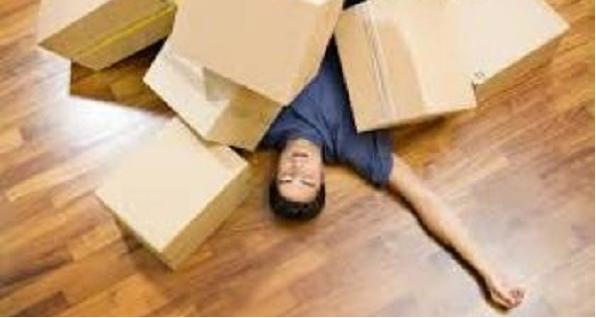 Man die gefrustreerd onder een stapel dozen ligt